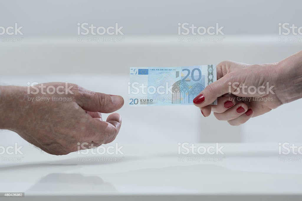 Handing an euro banknote stock photo