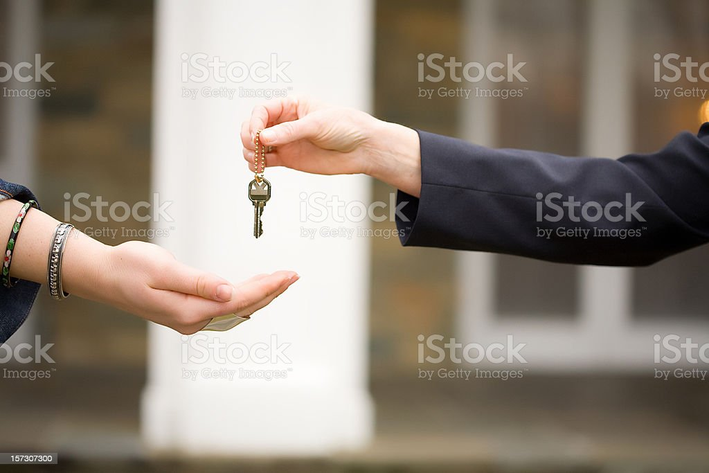 handing keys over in front of house stock photo