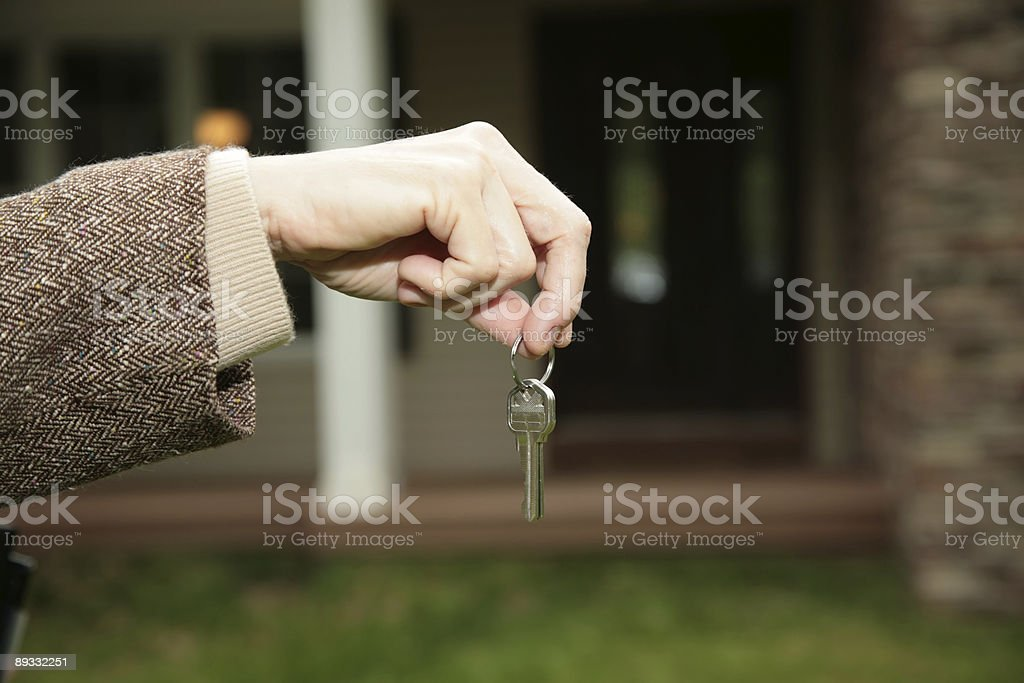 Handing keys over in front of house royalty-free stock photo