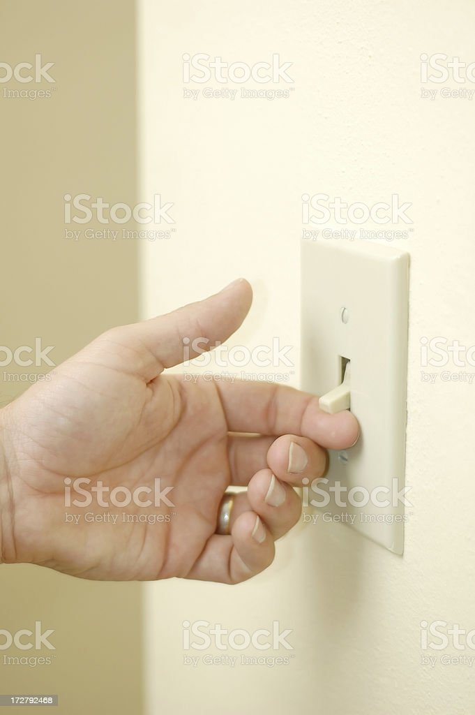Handing turning on wall light switch. stock photo