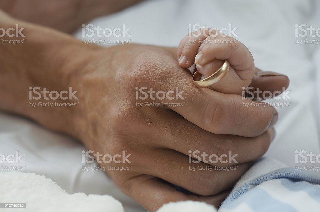Handle the baby with a ring in his father's arms stock photo