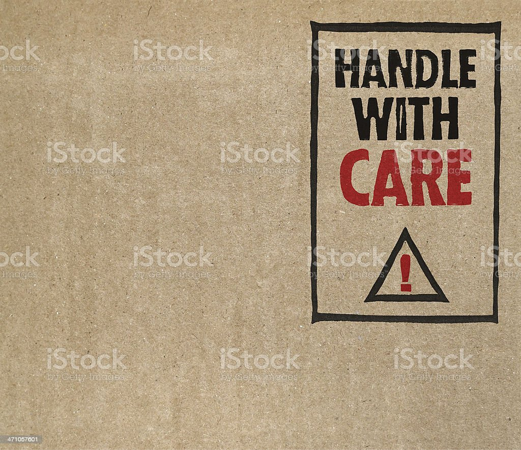 'Handle with care' on brown cardboard stock photo