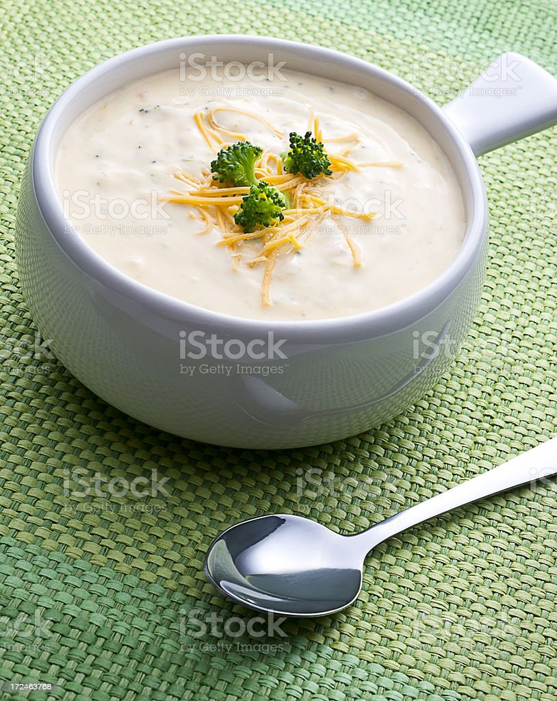 Handled bowl of cream of broccoli soup with cheese garnish stock photo