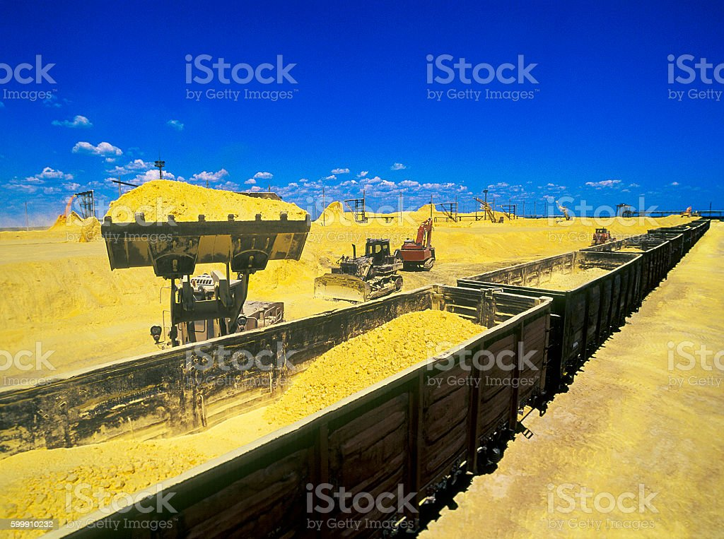 Handling of sulfur in industrial wagons stock photo
