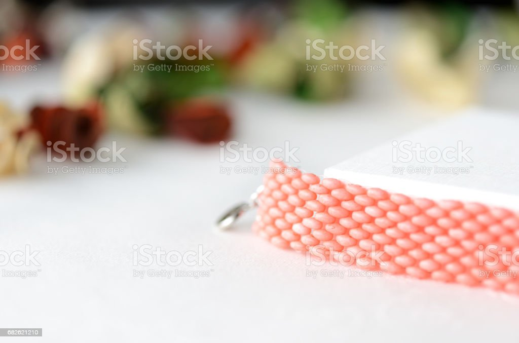 Handmade beaded bracelet coral color close up stock photo