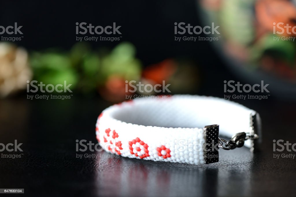 Handmade beaded bracelet with floral print on a dark background stock photo