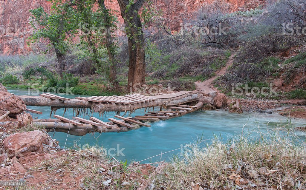 Hand-made bridge over small river in a canyon stock photo