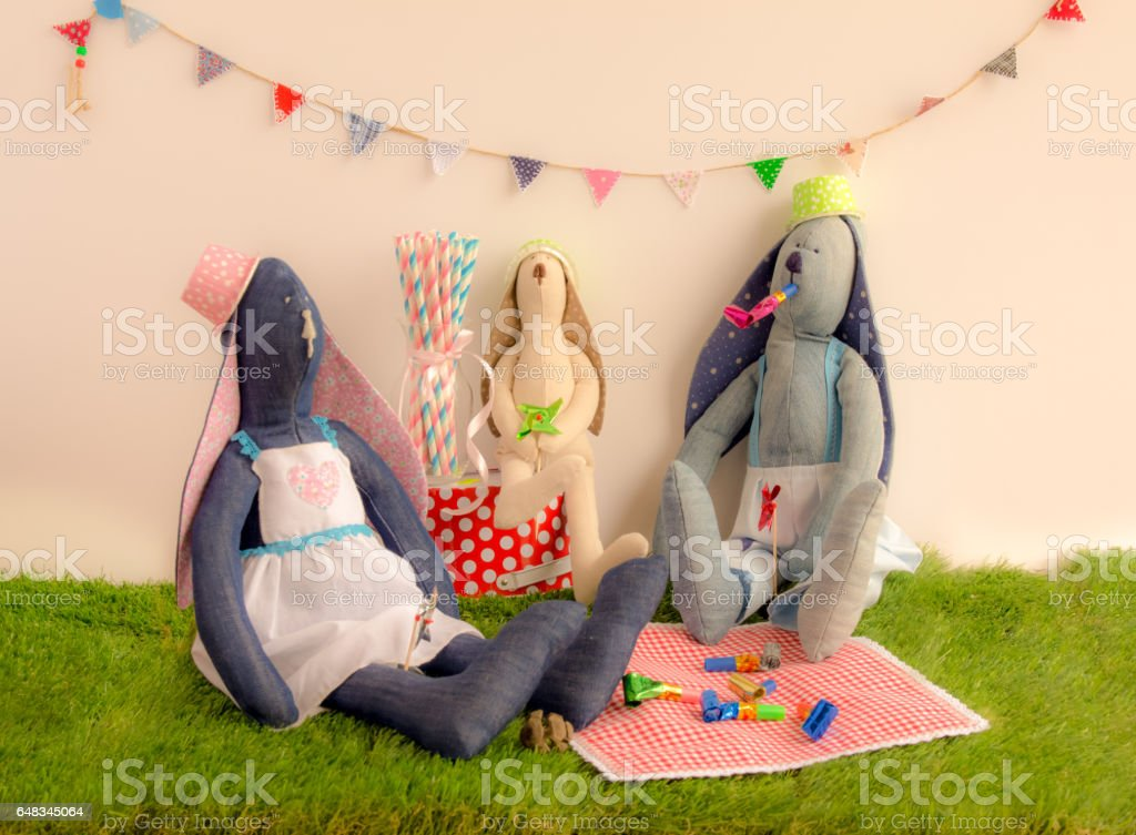 Handmade cloth rabbit dolls sitting on the grass and celebrating in party concept stock photo
