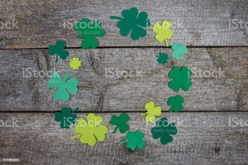Handmade clover leaves laid out on table in form of circle stock photo