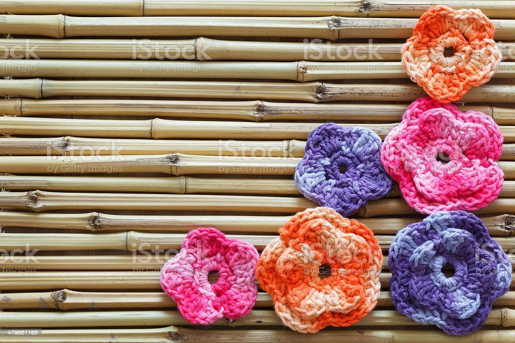 Handmade colorful crochet flowers on bamboo stock photo