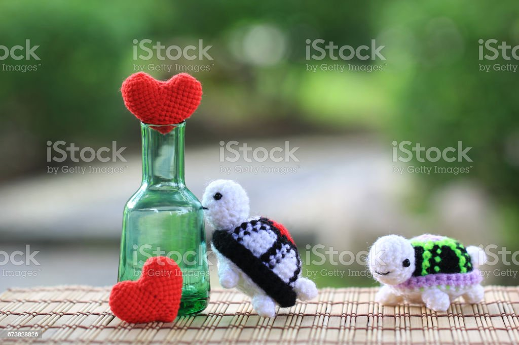 Handmade crochet heart and crochet doll turtle on green background, Valentine's Day stock photo