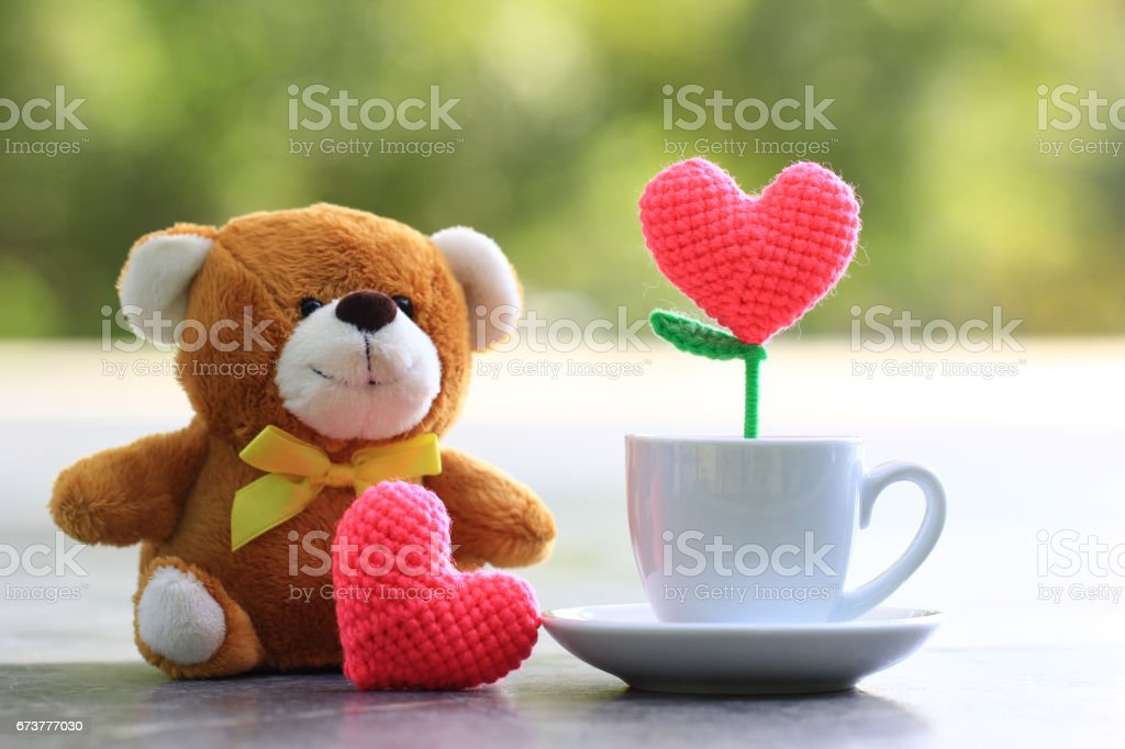 Handmade crochet heart in the white cup with Teddy bear for Happy valentine day concept stock photo