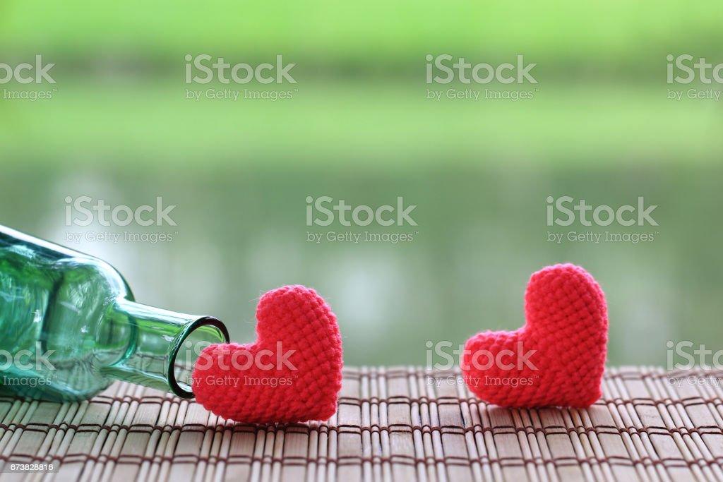 Handmade crochet heart on green background. stock photo