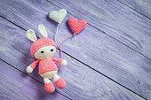 Handmade crochet rabbit toy with two heart balls.