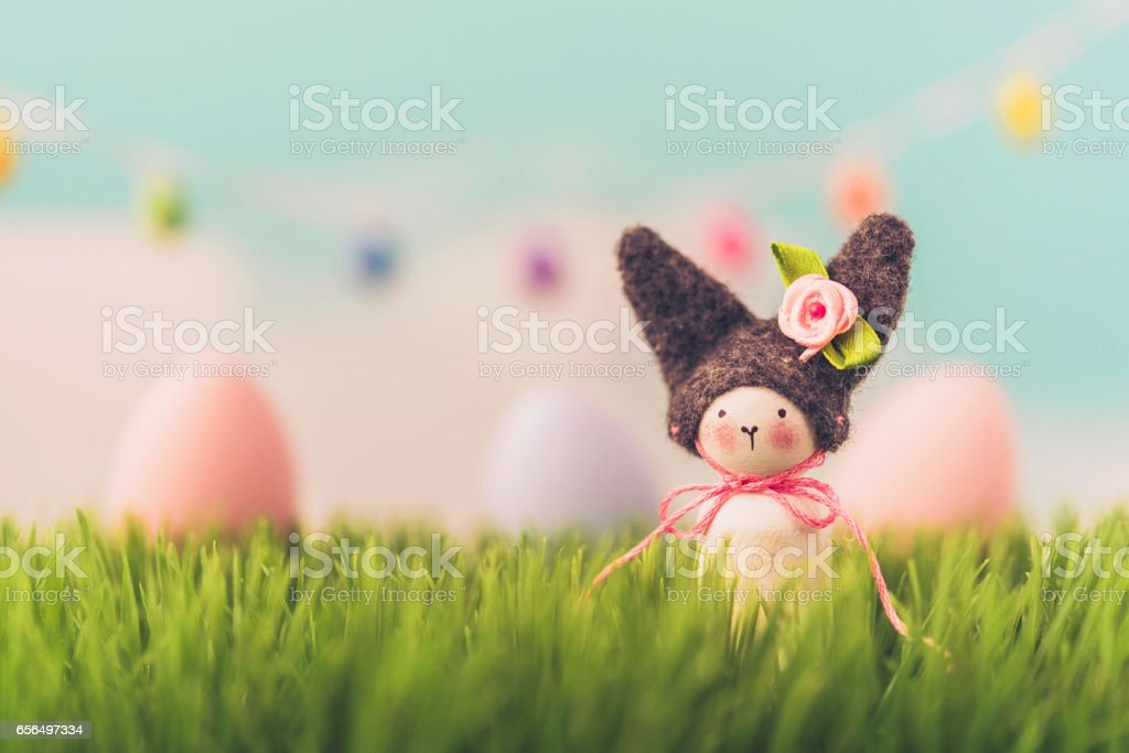 Handmade Easter bunny sitting in grass stock photo