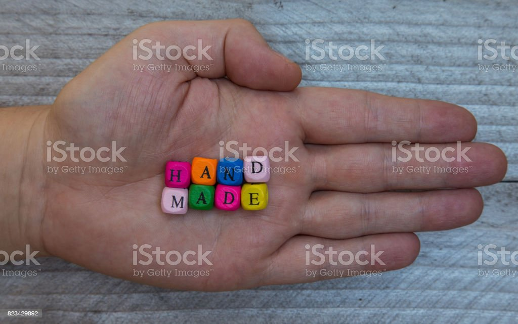 Handmade letter cube in hand on gray wood visualization stock photo