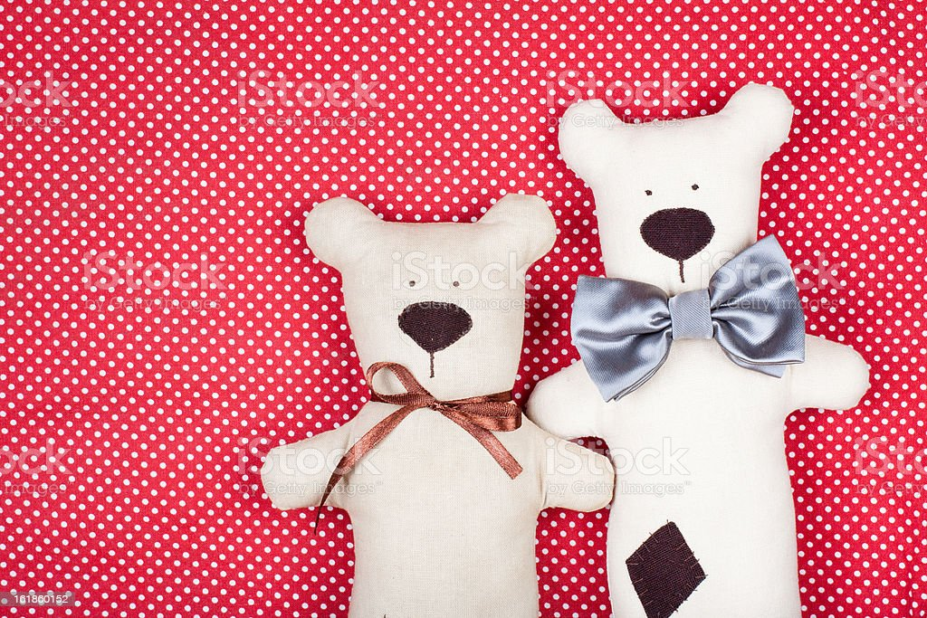 Handmade pair of bears on red textile texture background royalty-free stock photo
