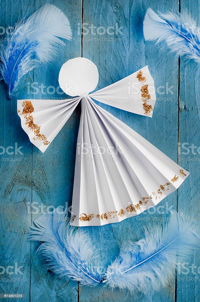 Handmade paper white angel on blue feather background. stock photo
