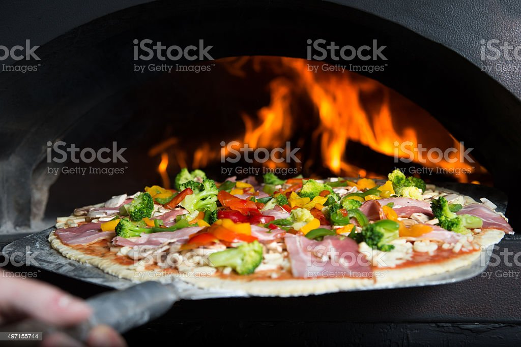 Handmade pizza is inserted to hot slove stock photo