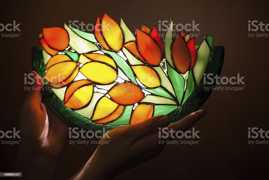Handmade stained glass lamp with tulips flowers in woman's hands stock photo