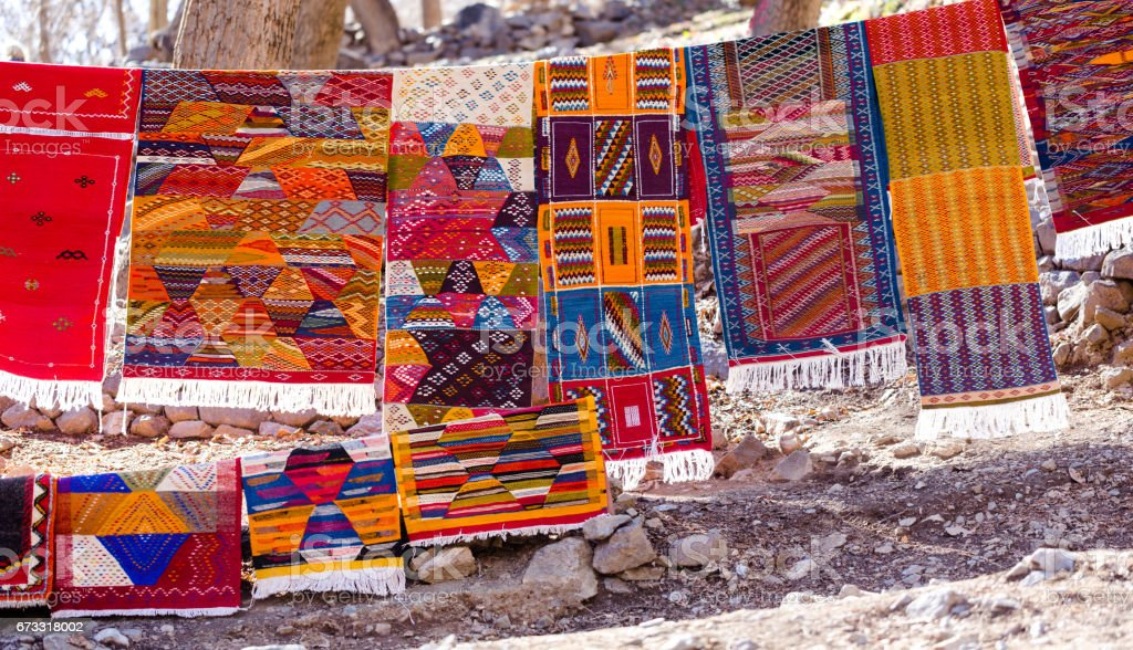 Handmade traditional in vibrant colors berber rugs hanged on line in berber village stock photo
