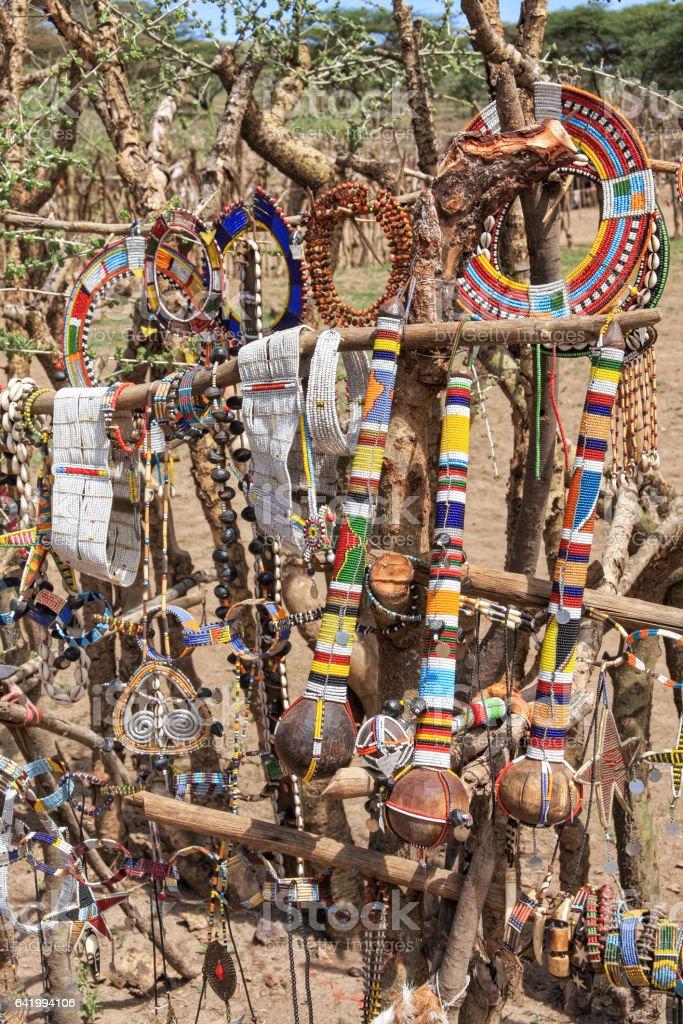 Handmade traditional Maasai souvenirs hanging on paling in village stock photo
