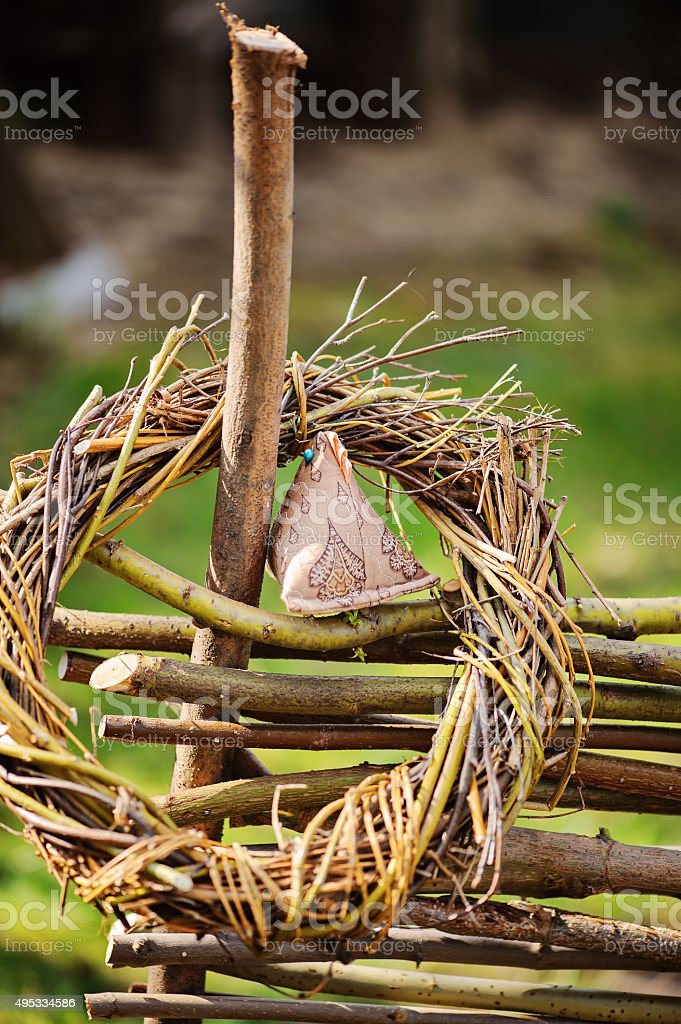 handmade wreath and chicken on osier wicker fence in garden stock photo
