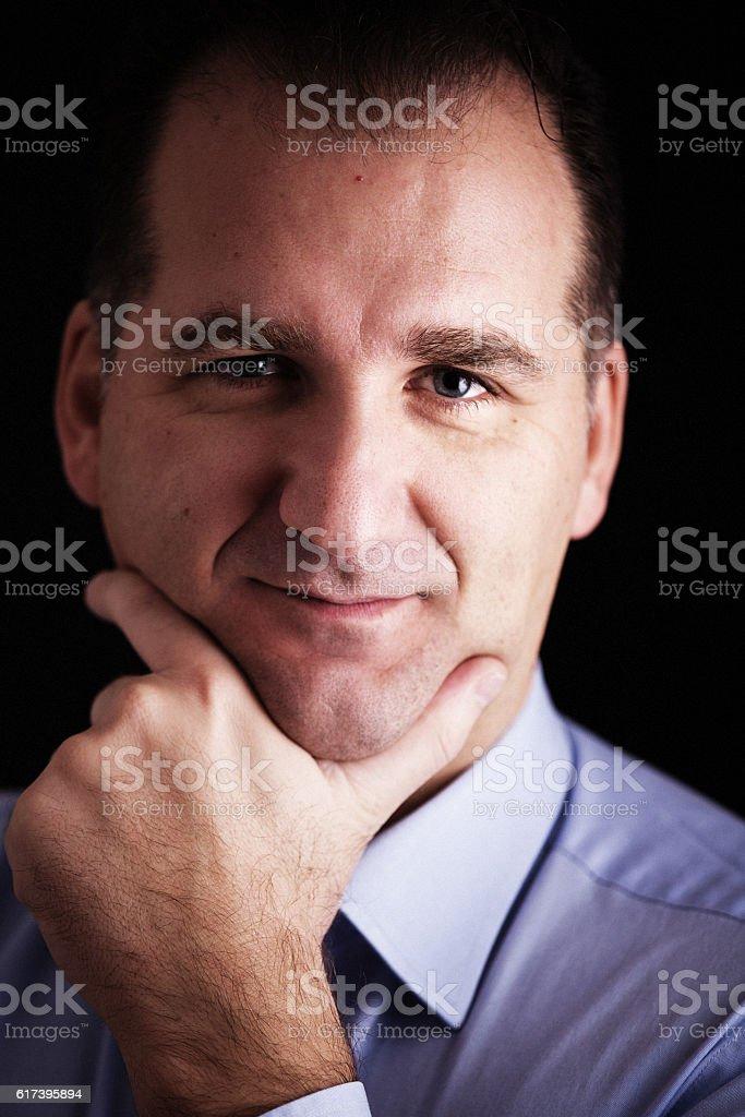 Hand-on-chin portrait of serene man stock photo