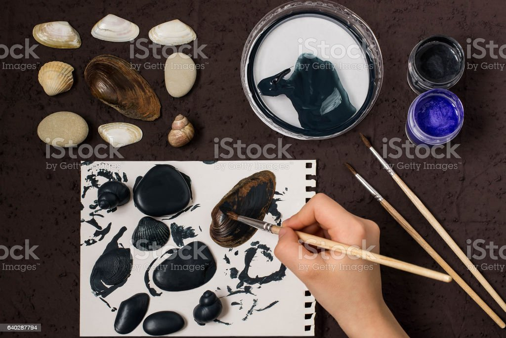 Hand-painted dot patterns on sea pebbles and shells. Step 2 stock photo