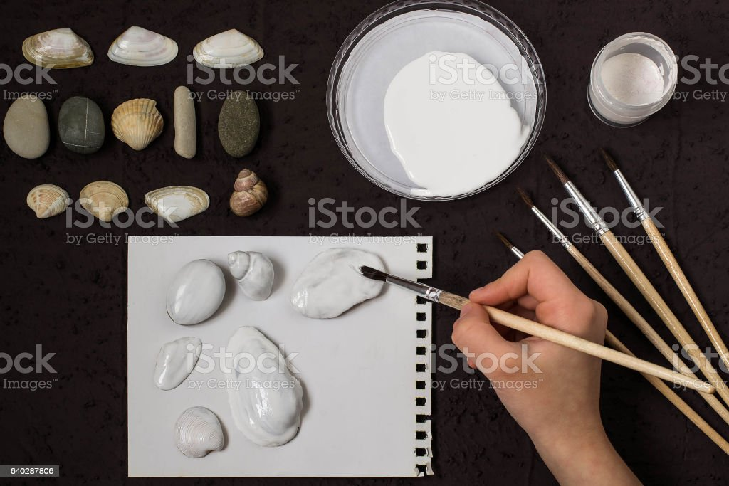 Hand-painted dot patterns on sea pebbles and shells. Step 3 stock photo