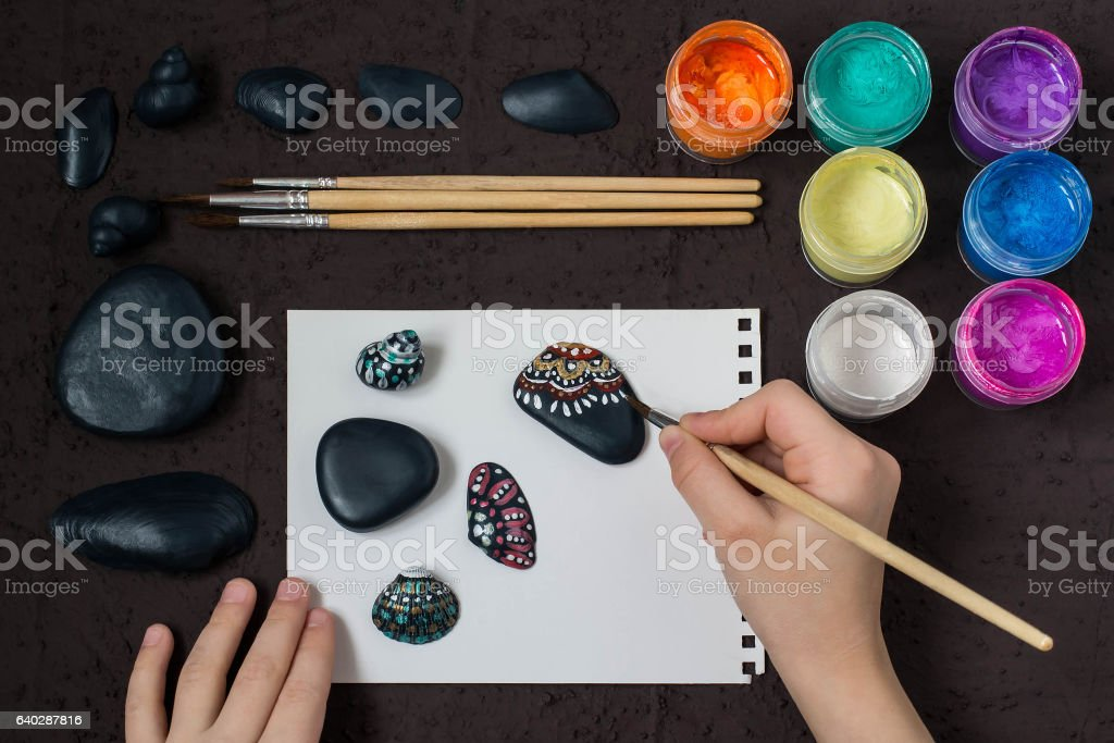 Hand-painted dot patterns on sea pebbles and shells. Step 4 stock photo
