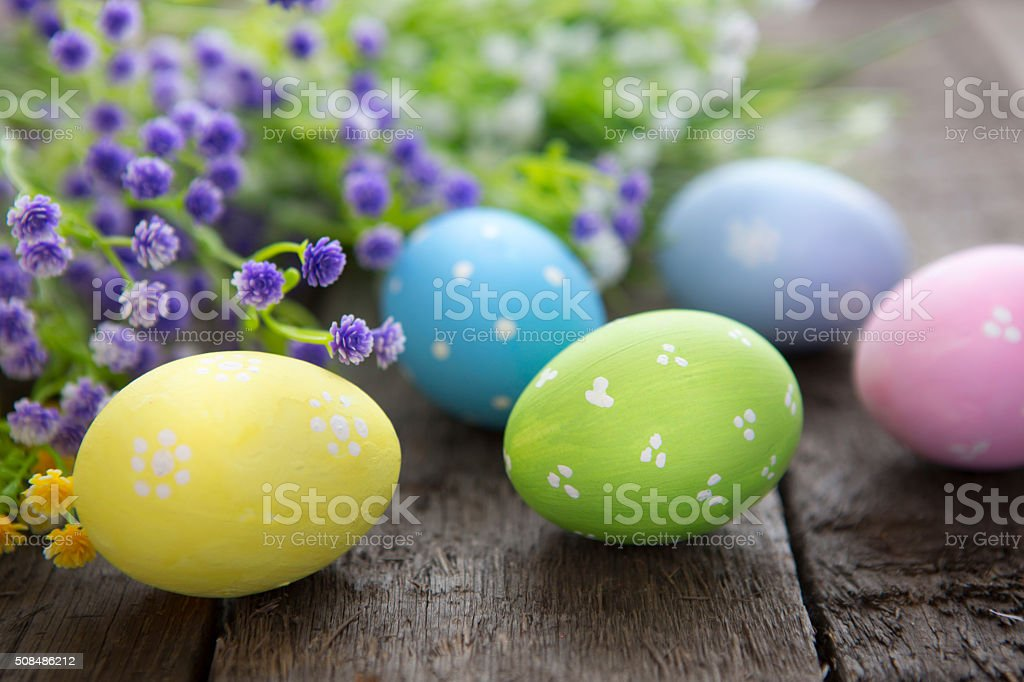 Hand-painted easter eggs with flowers on wooden background