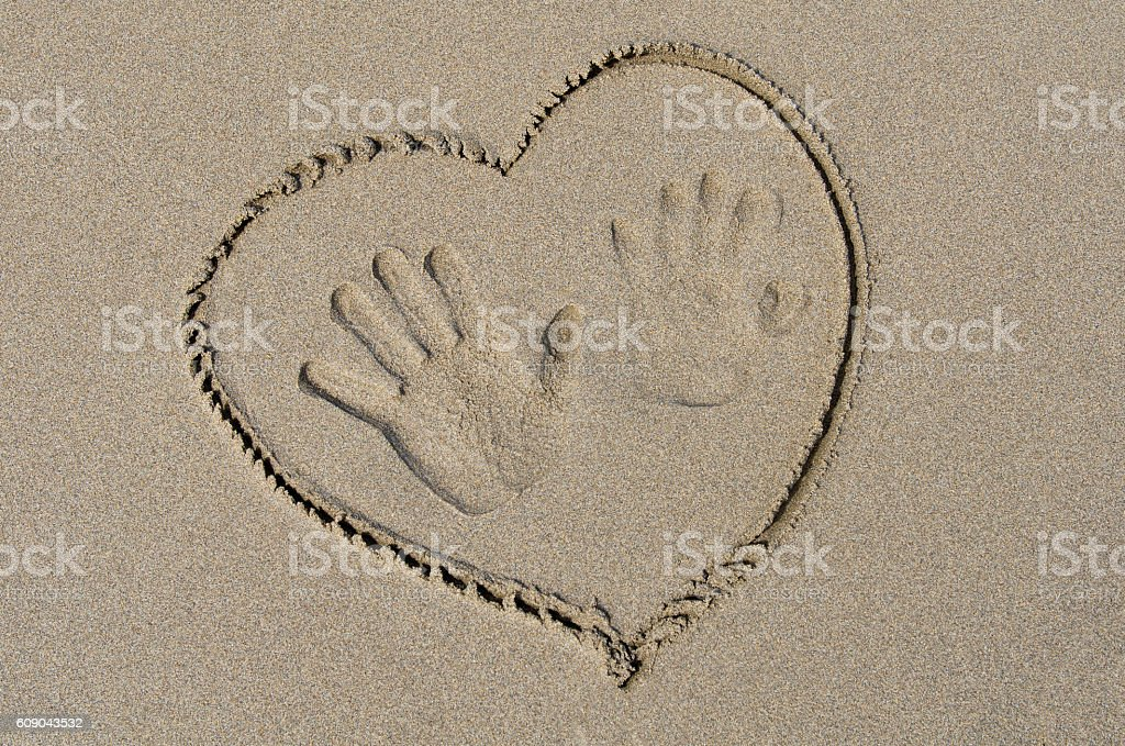 Handprints and heart drawn on the sand stock photo
