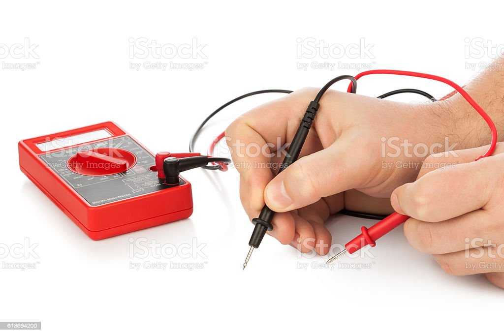Hands and electric multimeter stock photo