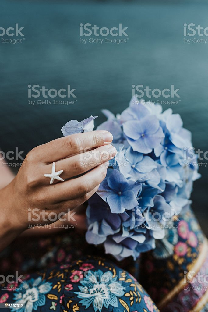 Hands and flowers by the sea stock photo