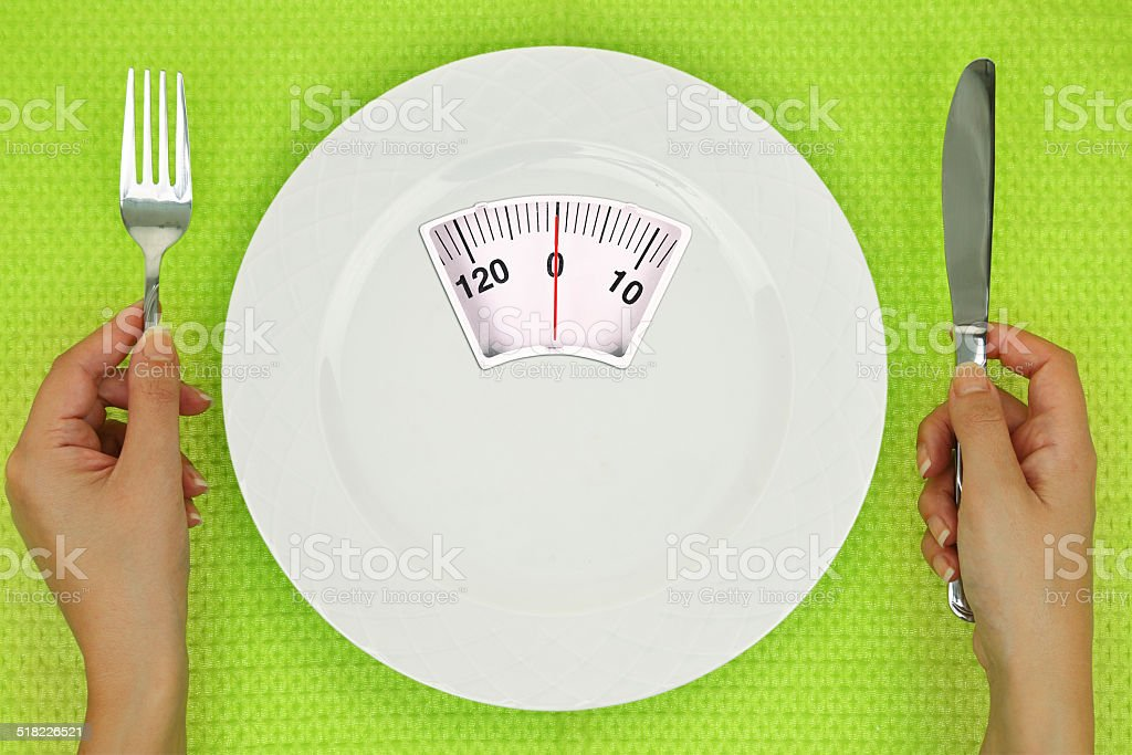 Hands and plate with weighing scale on the table stock photo