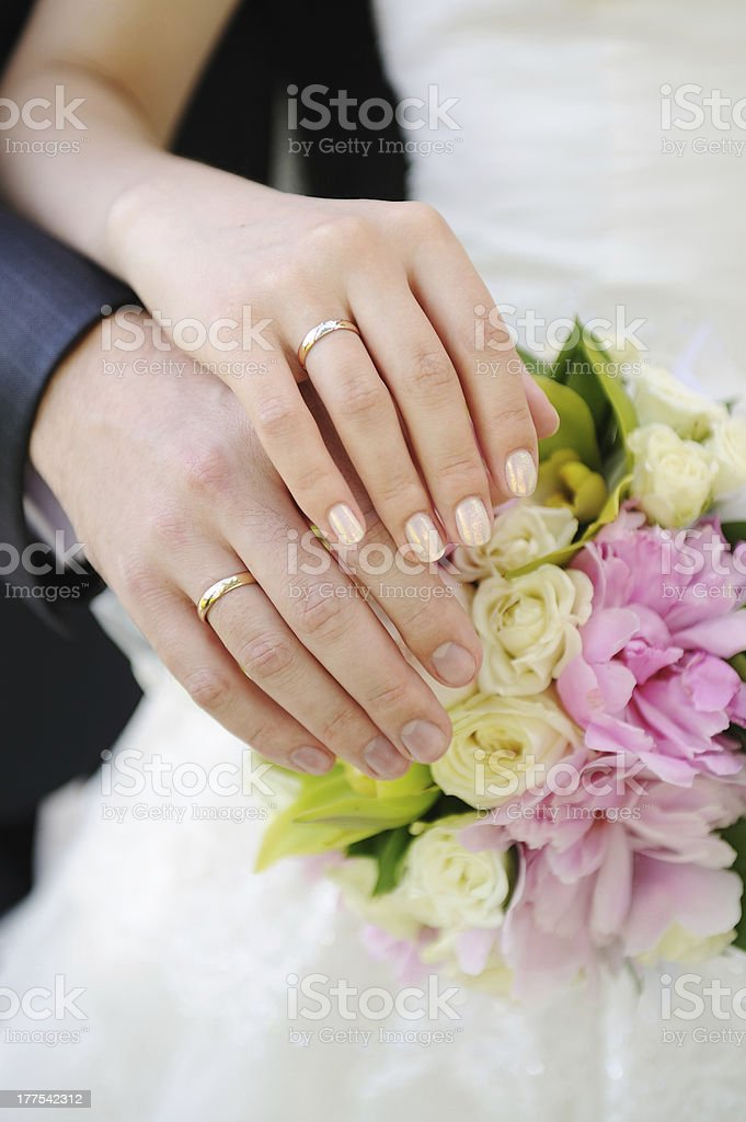 Hands and rings on wedding bouquet royalty-free stock photo