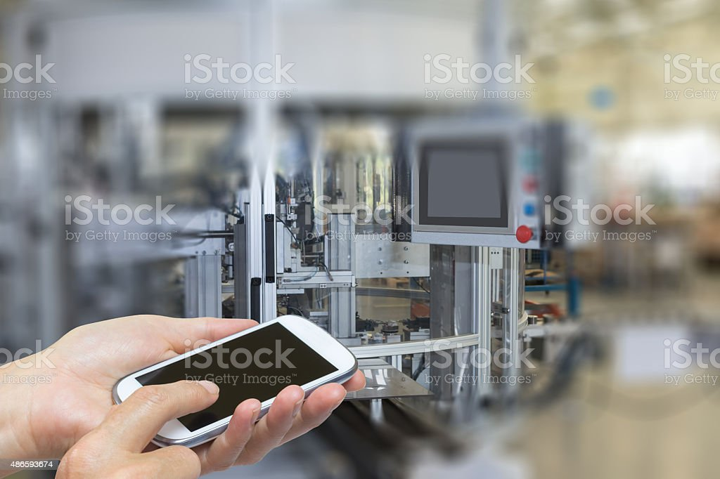 Hands and smart phone in industry interior stock photo