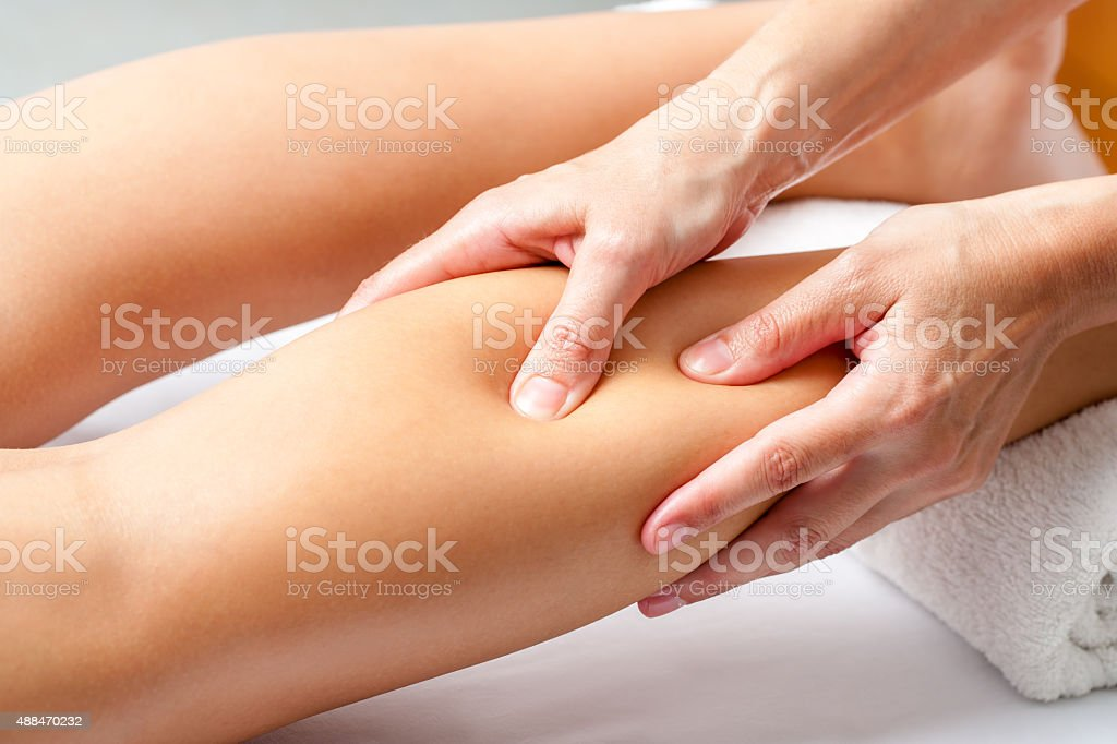 Hands applying pressure with fingers on calf muscle. stock photo