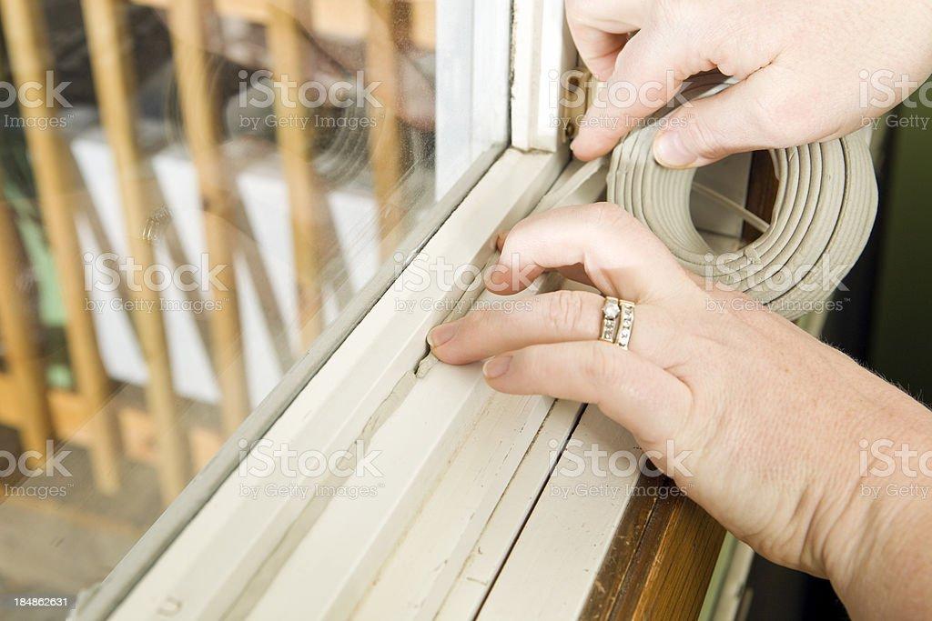 Hands Applying Weather Seal Caulk to Window Frame stock photo