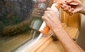 Hands Applying Weather Seal Caulk to Window Frame