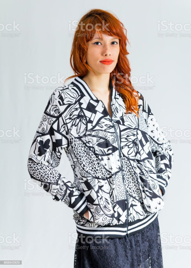 Hands are in your pocket. She is facing the camera. Young redhead woman wears floral pattern jacket. Black and white. White background. stock photo