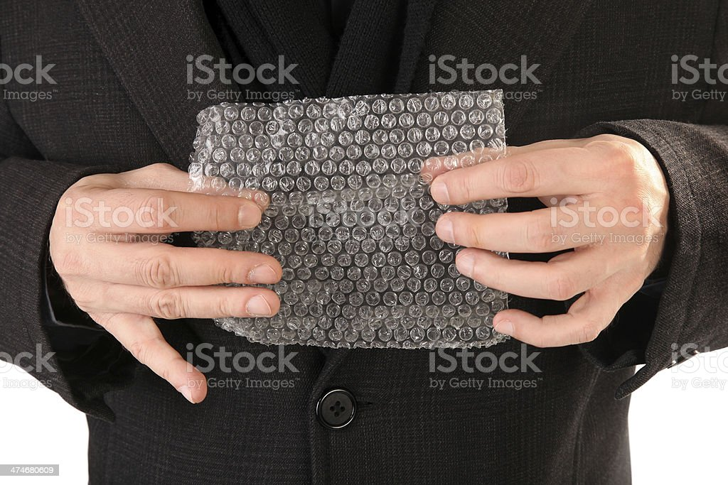 Hands are popping bubble wrap sheet stock photo