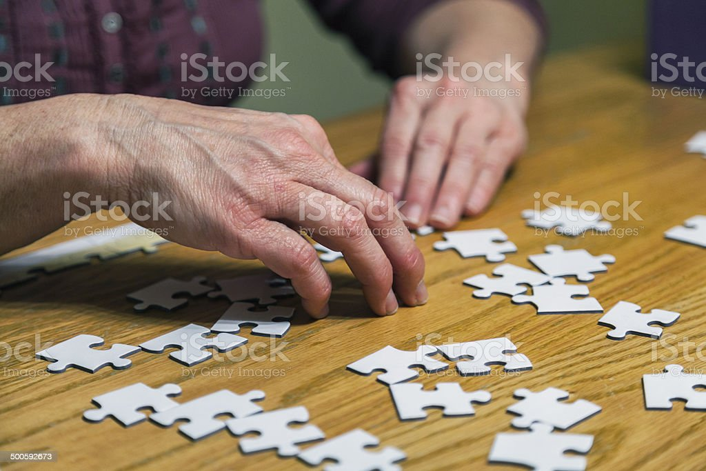 Hands Assembling Jigsaw Puzzle royalty-free stock photo