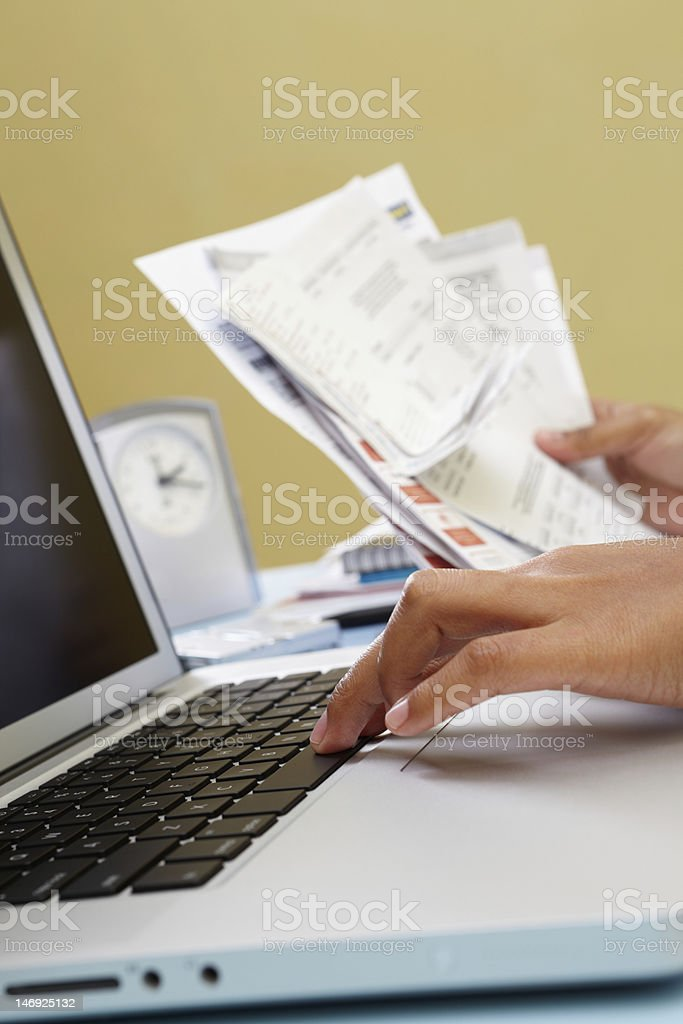Hands at laptop holding receipts representing e-commerce stock photo