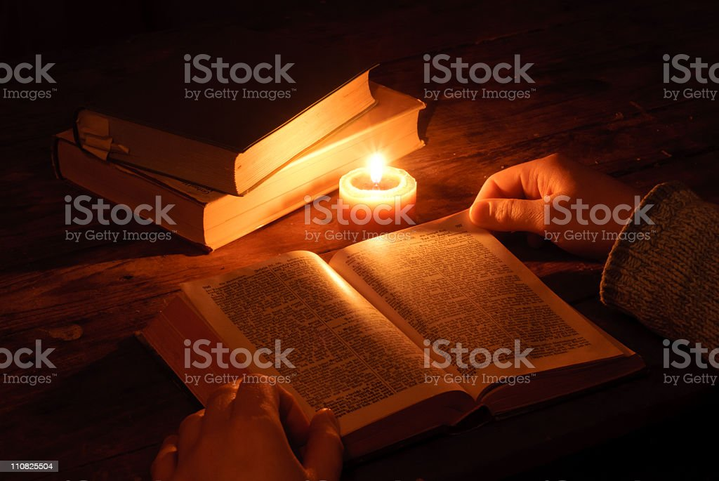 Hands beside a bible in candlelight royalty-free stock photo