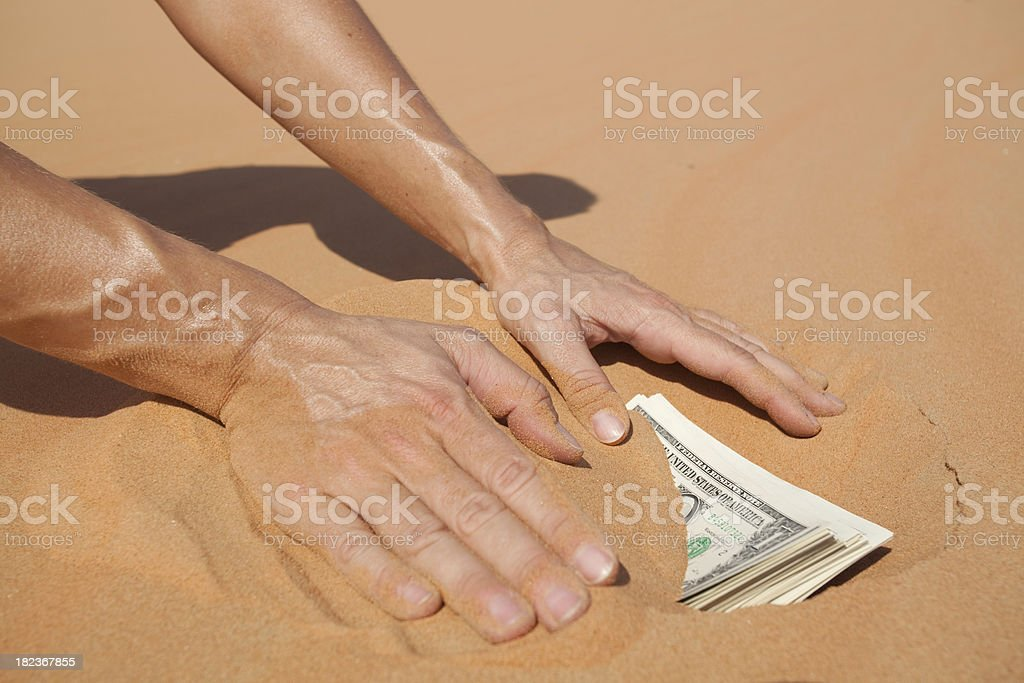 hands burying dollars stock photo