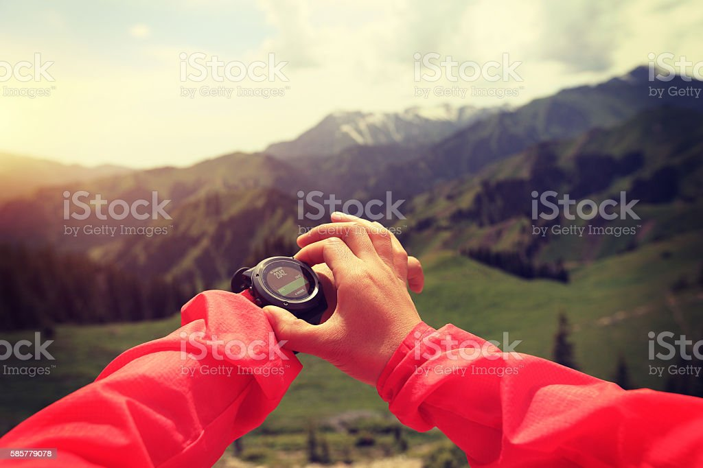 hands checking the altimeter on sports watch at mountain peak stock photo