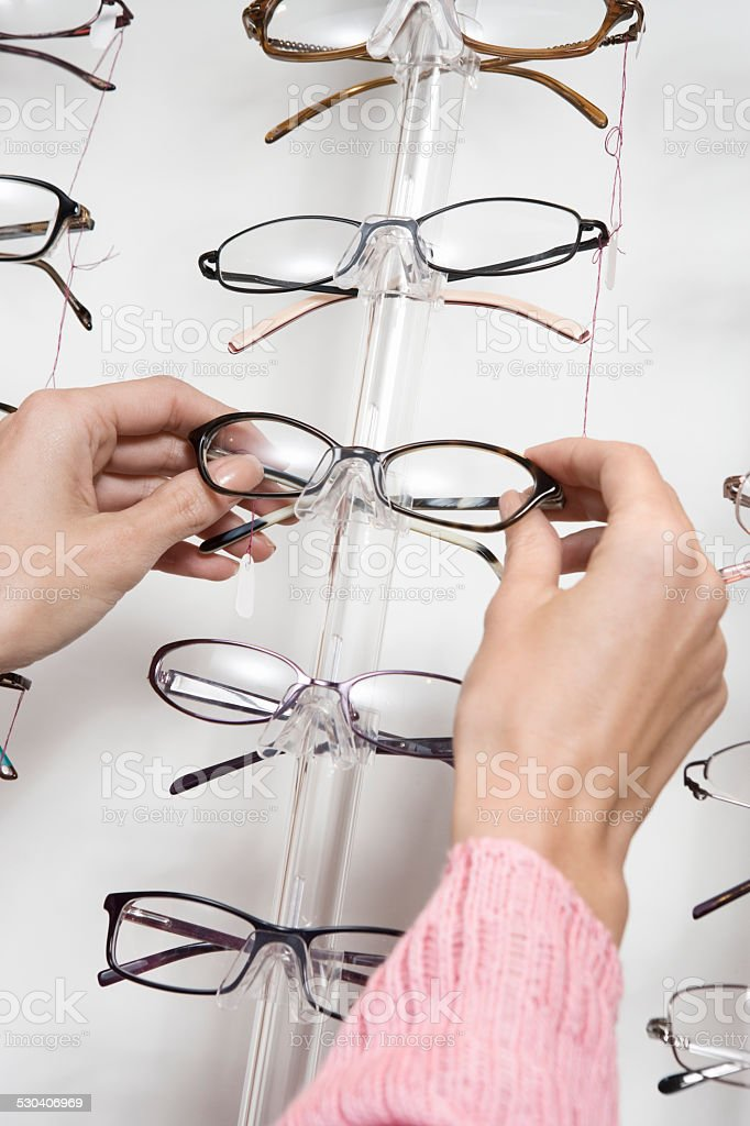 Hands Choosing Eyeglasses From Rack stock photo