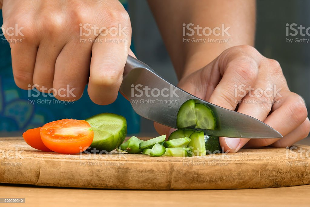 hands chopping cucumbers and tomatoes stock photo